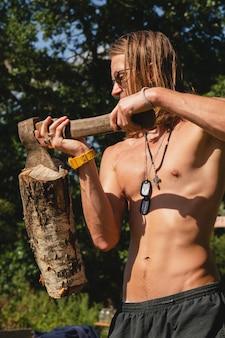 Кринит сексуальный парень, держащий дровокол, застрявший в бревне.