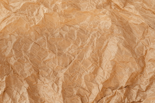 Crinkled wrap sheet, recycle grunge texture sample. closeup of parchment canvas. wrapping paper material. kraft paper texture. brown crumpled surface.