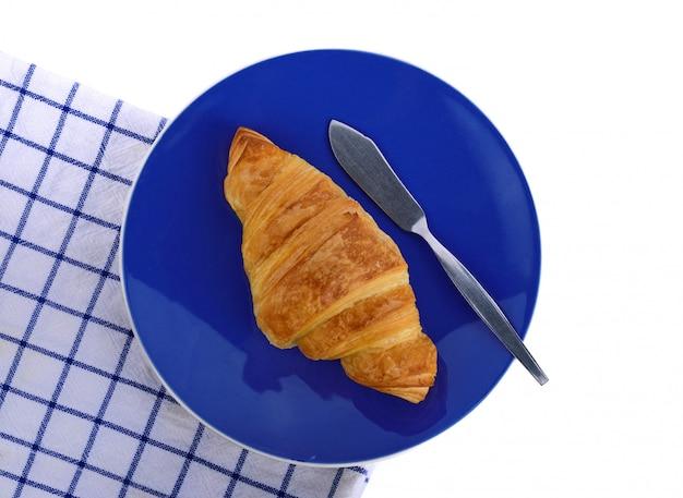 Criossant положить на тарелку с тканью на белом фоне
