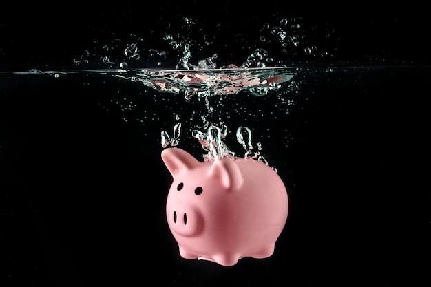 Crisis concept, drowning piggy bank