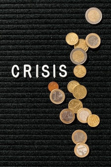 Crisis word and coins flat lay