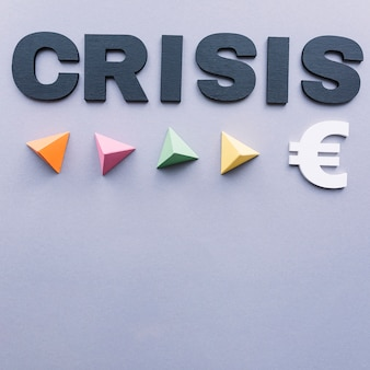 Crisis word with colorful triangular pyramids and euro sign on grey background