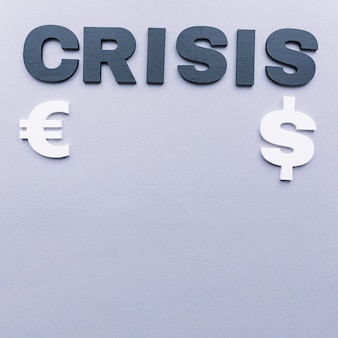 Crisis word with euro and dollar symbol on grey background