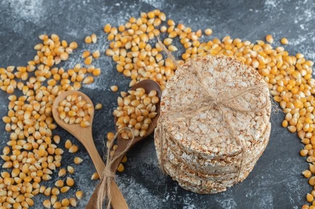 未調理のポップコーンシードの木のスプーンでロープでカリカリのパン。