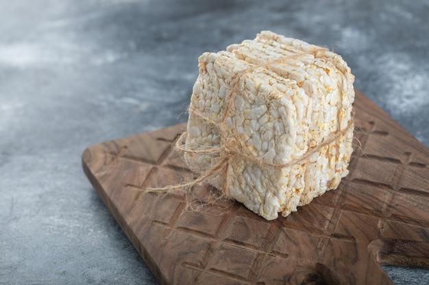 Crisp bread in rope on wooden cutting board.