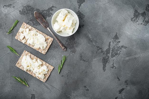 회색 돌 테이블 배경에 크림 치즈 세트로 바삭 바삭한 빵, 텍스트 복사 공간 평면도 평면 누워