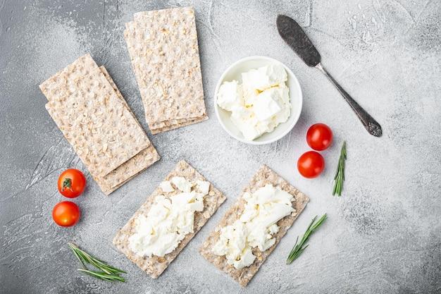 크림 치즈 세트가 있는 바삭한 빵, 회색 돌 탁자 배경, 위쪽 전망 평면