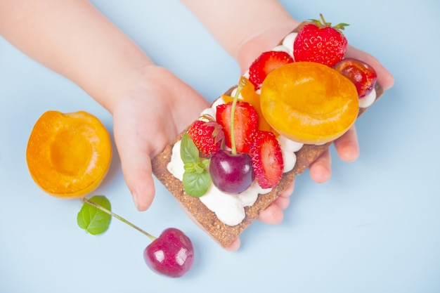 Crisp bread with creme cheese, fruit and berries in a child hand
