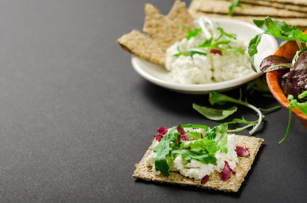 Crisp bread with mix of fresh greens and cream cheese on a black background