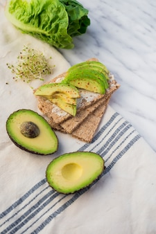 Crisp bread with sliced avocado on table