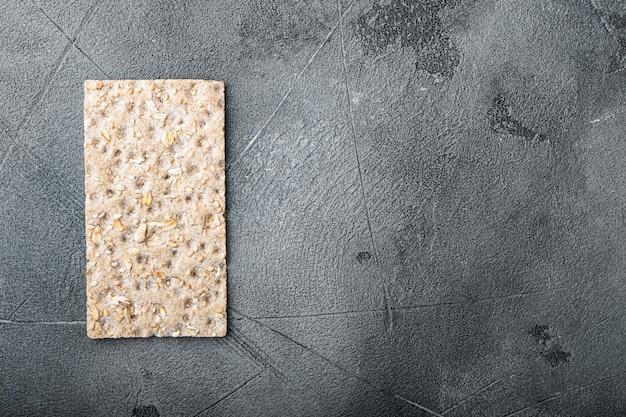 Хрустящий хлеб с набором семян подсолнечника, чиа и кунжута, на сером каменном столе, плоский вид сверху