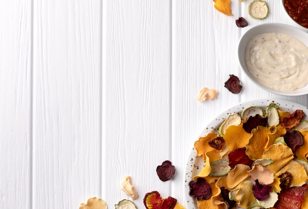 Crisp crunchy organic vegetable chips with oven-baked pumpkin, beetroot, tomato, carrot chips snacks with sauce on a white wooden table
