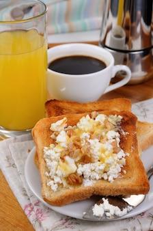 오렌지 주스와 커피와 함께 아침 식사로 신선한 토스트 리코타 꿀과 견과류