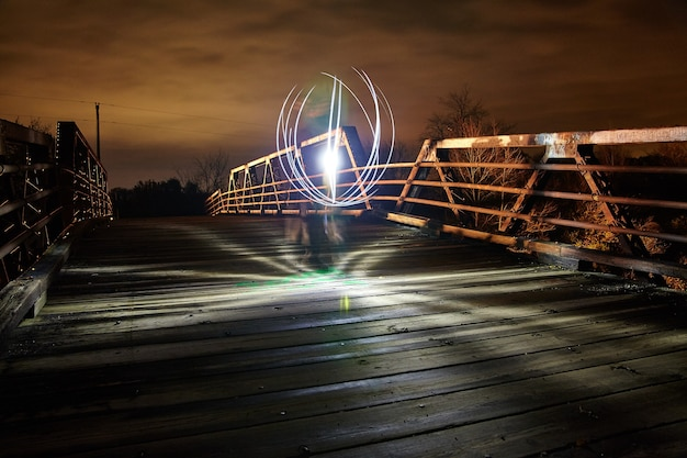 Crisp glowing white light floats on a metal bridge at dusk