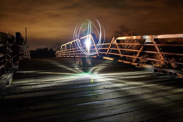 夕暮れ時に金属製の橋にくっきりと輝く白い光が浮かぶ