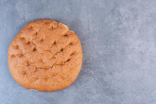 Хрустящий круглый буханка хлеба на мраморном фоне. фото высокого качества