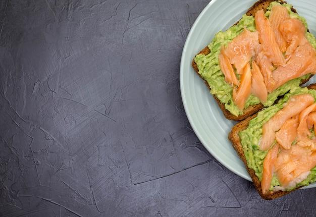 아보카도와 연어를 곁들인 바삭 바삭한 샌드위치. 어두운 호밀 빵, 아보카도 소스, 훈제 연어와 토스트의 근접 촬영. 복사 공간 대리석 배경입니다. 건강한 음식, 미식가, 아침, 점심. 선택적 초점.