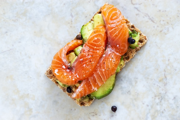 Crisp sandwiches with avocado and salmon. marble background.