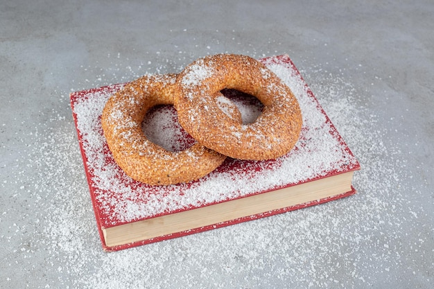 Crisp sesame coated bagels on a tray covered in coconut powder on marble surfaceq