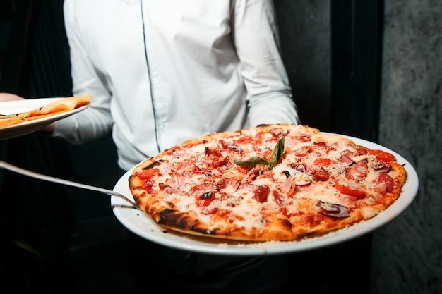 Горячая пицца с плавленым сыром, помидорами и ветчиной. подается на белой круглой тарелке. crisp.