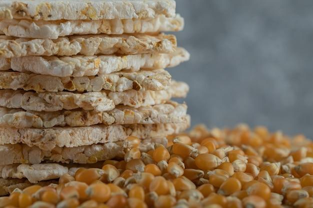 Хрустящие хлебцы и сырые семена кукурузы на деревянной доске