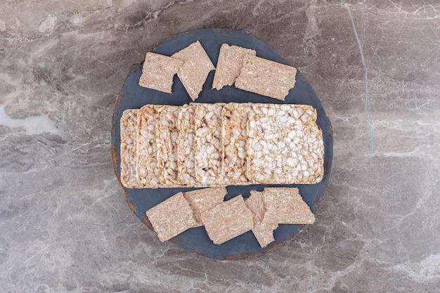 Fette biscottate e gallette di riso soffiato in vassoio, sulla superficie di marmo