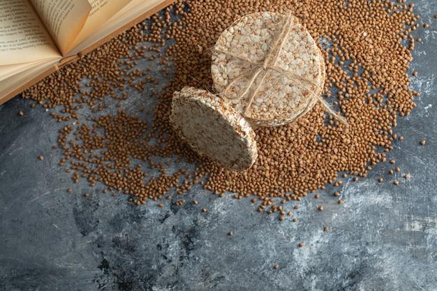 Хлебцы, сырая гречка и книга на мраморной поверхности