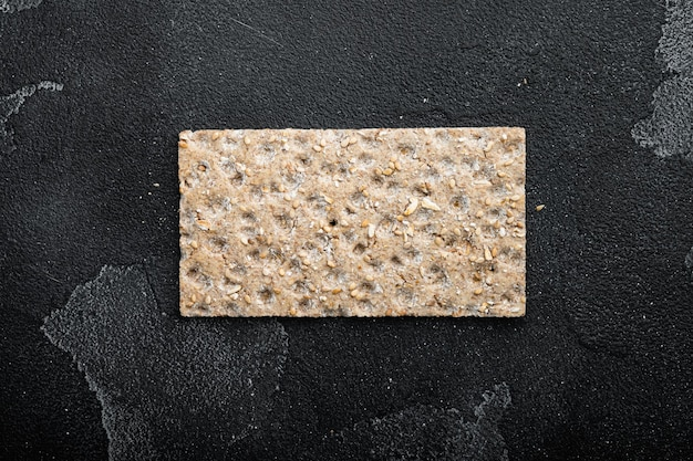 Crispbread with sunflower, chia and sesames seeds set, on black dark stone table background, top view flat lay, with copy space for text