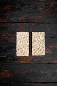 Crispbread with sunflower, chia and sesames seeds set, on old dark wooden table, top view flat lay