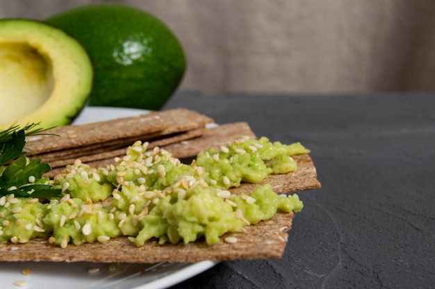 Crispbreads with mashed avocado and sesame seed