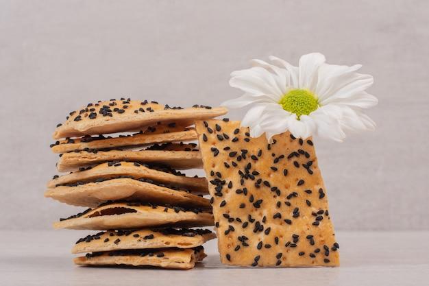 Pezzi di pane croccante con semi di sesamo nero su fondo bianco con fiore.