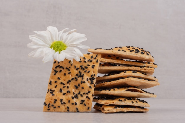 Crispy bread pieces with black sesame seeds on white with flower.