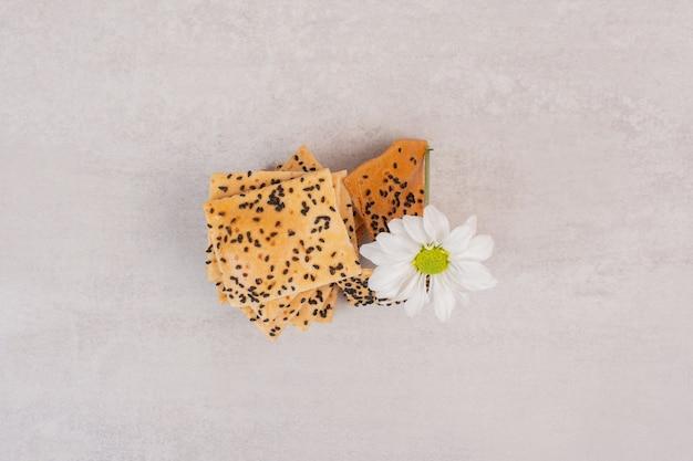 꽃과 함께 검은 깨와 바삭한 빵 조각.