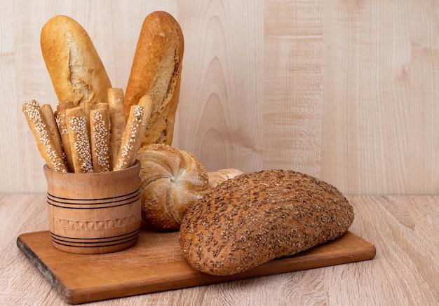 바삭 바삭한 빵은 나무 판에 참깨와 밀기울 빵이 붙어 있습니다. 프랑스 바게트. 나무 배경에 다른 품종.