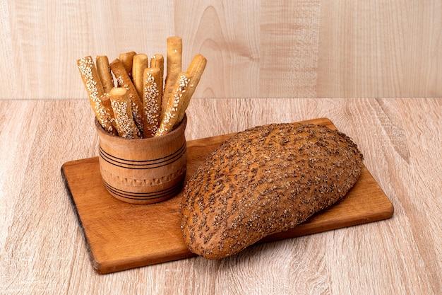 바삭 바삭한 빵은 나무 판에 참깨와 밀기울 빵이 붙어 있습니다.