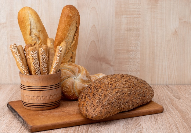 Crispy bread sticks with sesame seeds and bran bread on a wooden board. french baguettes. different breeds on wooden background.