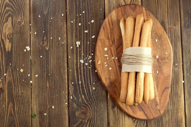 Crispy bread sticks on wooden table