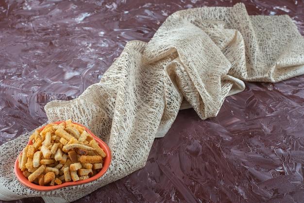 대리석 테이블에 식탁보에 그릇에 바삭한 빵 부스러기.