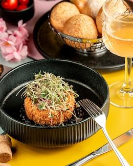 Tortino di pollo impanato croccante condito con erbe in una ciotola nera