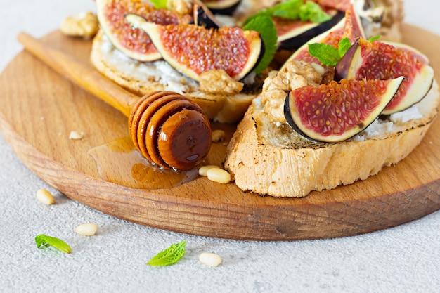 Хрустящая брускетта с мягкой рикоттой, спелым инжиром, грецкими и кедровыми орехами, мятой и медом на светлом фоне. фруктовый тост из инжира на деревянной доске с медом и грецким орехом.