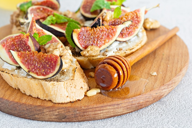Хрустящая брускетта с мягкой рикоттой, спелым инжиром, грецкими и кедровыми орехами, мятой и медом на светлом фоне.