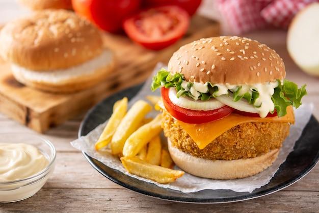 Хрустящий куриный бургер с сыром и картофелем на деревянном столе