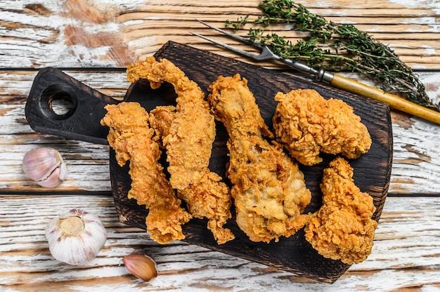 サクサクした鶏のドラムスティック、脚、翼、胸肉のストリップ。白い木製の背景。上面図。