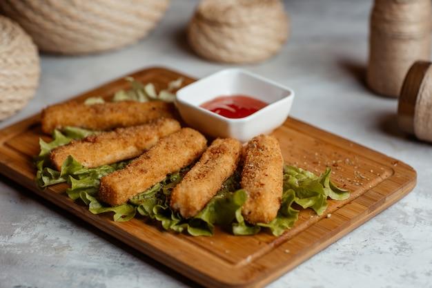 Хрустящие куриные закуски, палочки с кетчупом на деревянной доске с деревенскими корзинами вокруг