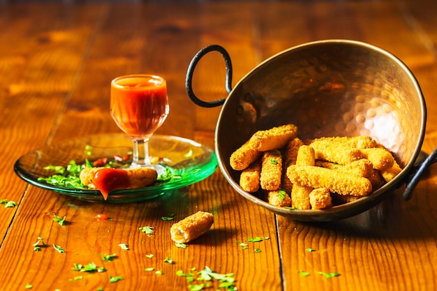 Crispy chicken fingers in copper utensil with sauce on wooden table