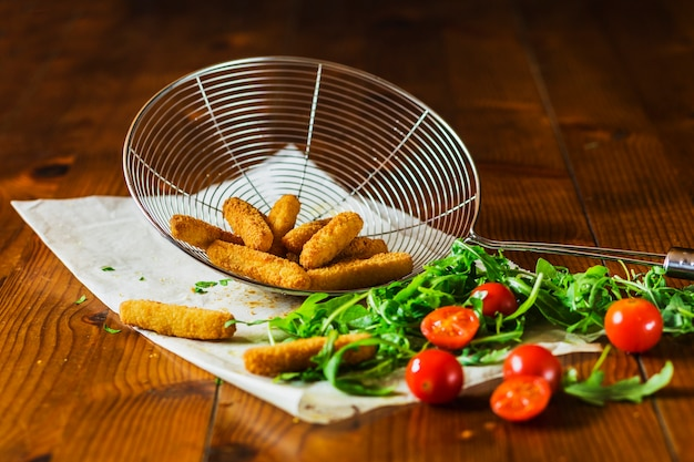 Crispy chicken fingers in skimmer with cherry tomatoes and leafy vegetable on table