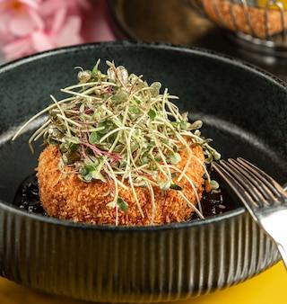 Crispy chicken nugget garnished with fresh herbs