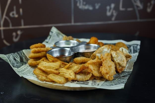 カリカリのチキンナゲット、フライドオニオンリング、チーズソースとマッシュルームソース、カフェのテーブルにケチャップを添えたゴールデンポテトスライスのフライ。ビールのおやつ。ファストフード