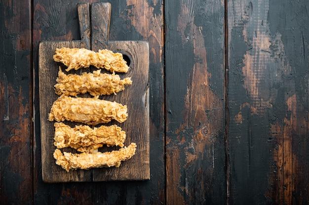 Хрустящие куриные вырезки на темном деревянном столе, плоская кладка.