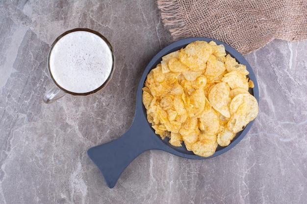Хрустящие чипсы на темной доске с бокалом пива. фото высокого качества
